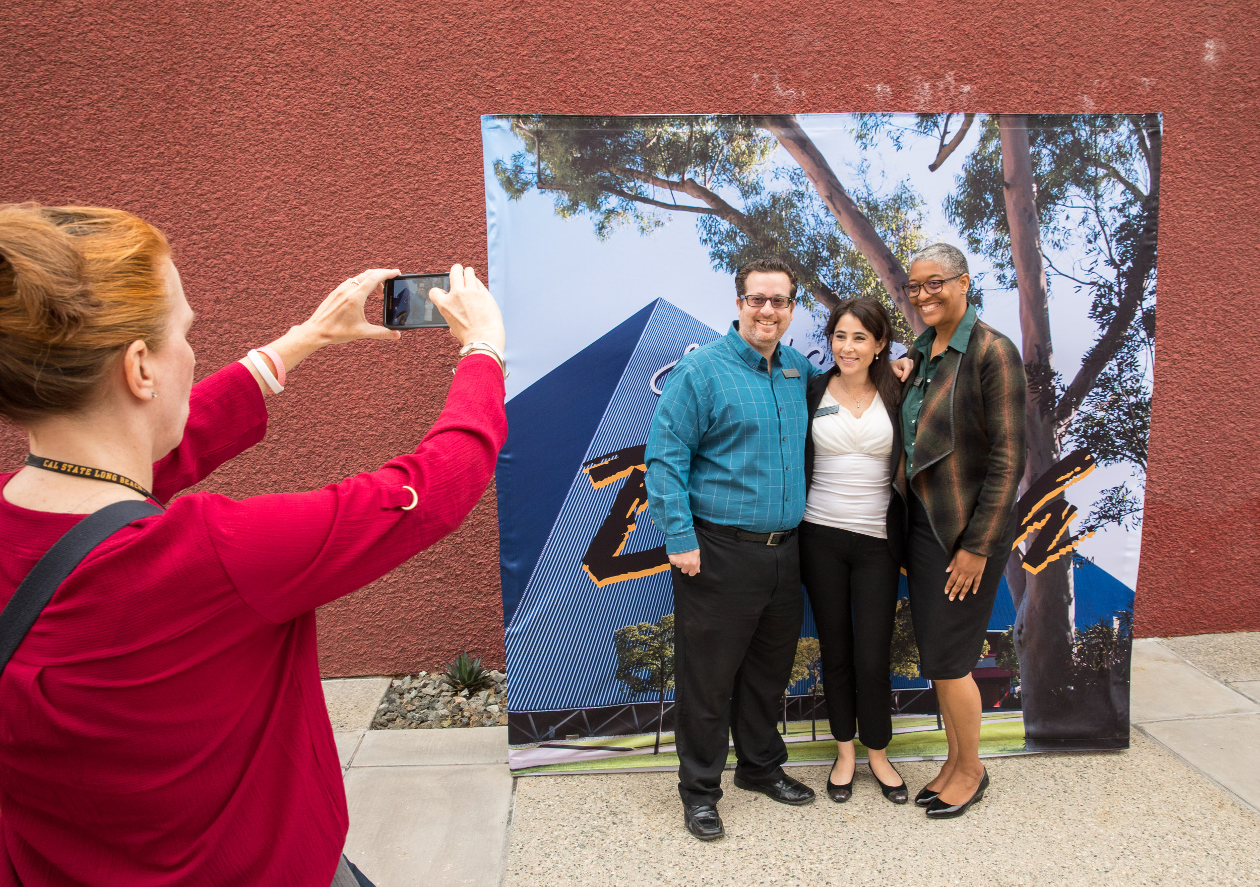 Guests take pictures in front of Pyramid banner