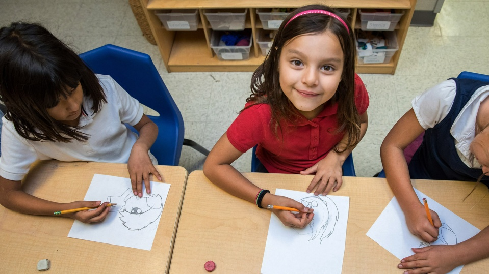 Child looks up while drawing at Isabel Patterson Center