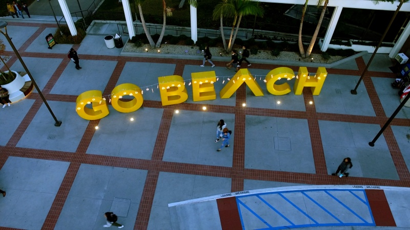 Students walk past the Go Beach sign adorned with holiday lights.