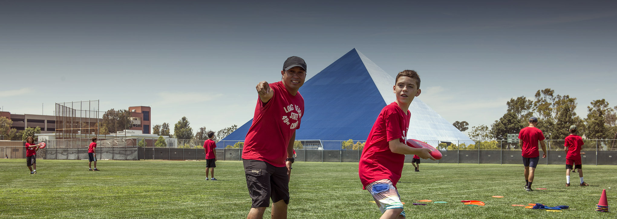 Page banner: young students playing ball on campus field, pyramid is seen in the background.
