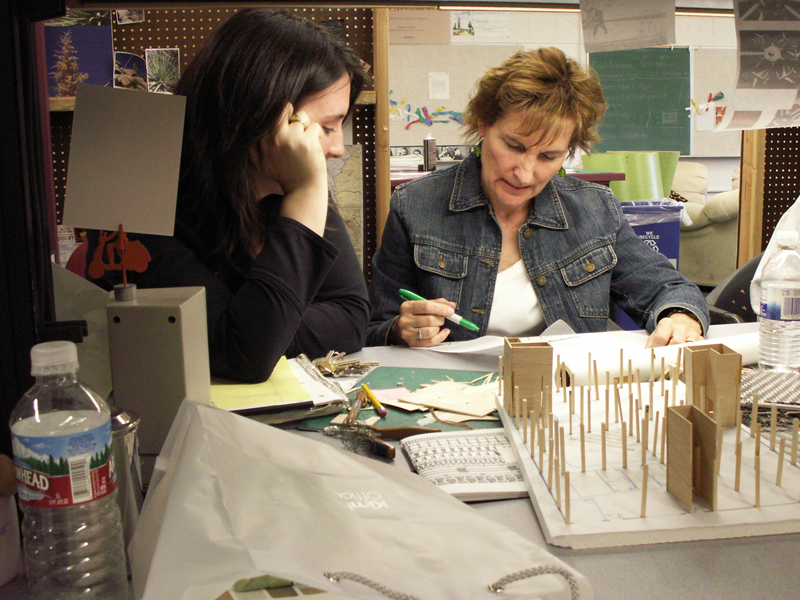 Design students receive feedback and information from faculty member