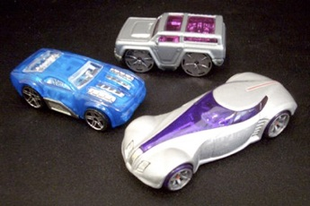 Three toy cars sit on top of a black backdrop.