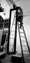 A black and white photograph showing a man on a ladder.