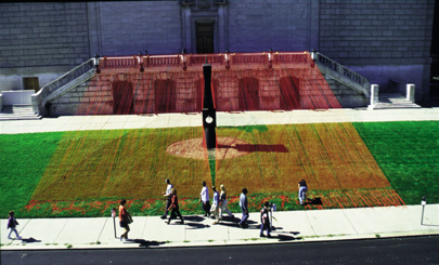 An art installation of many red strings strung across a green lawn.